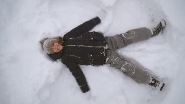 Little girl making snow angel in winter time.