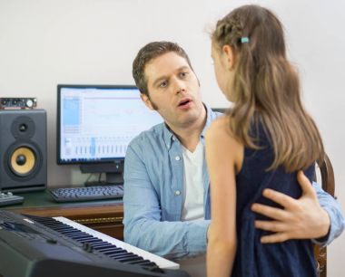 Male vocal coach teaching little girl how to sing. Focused on teacher.