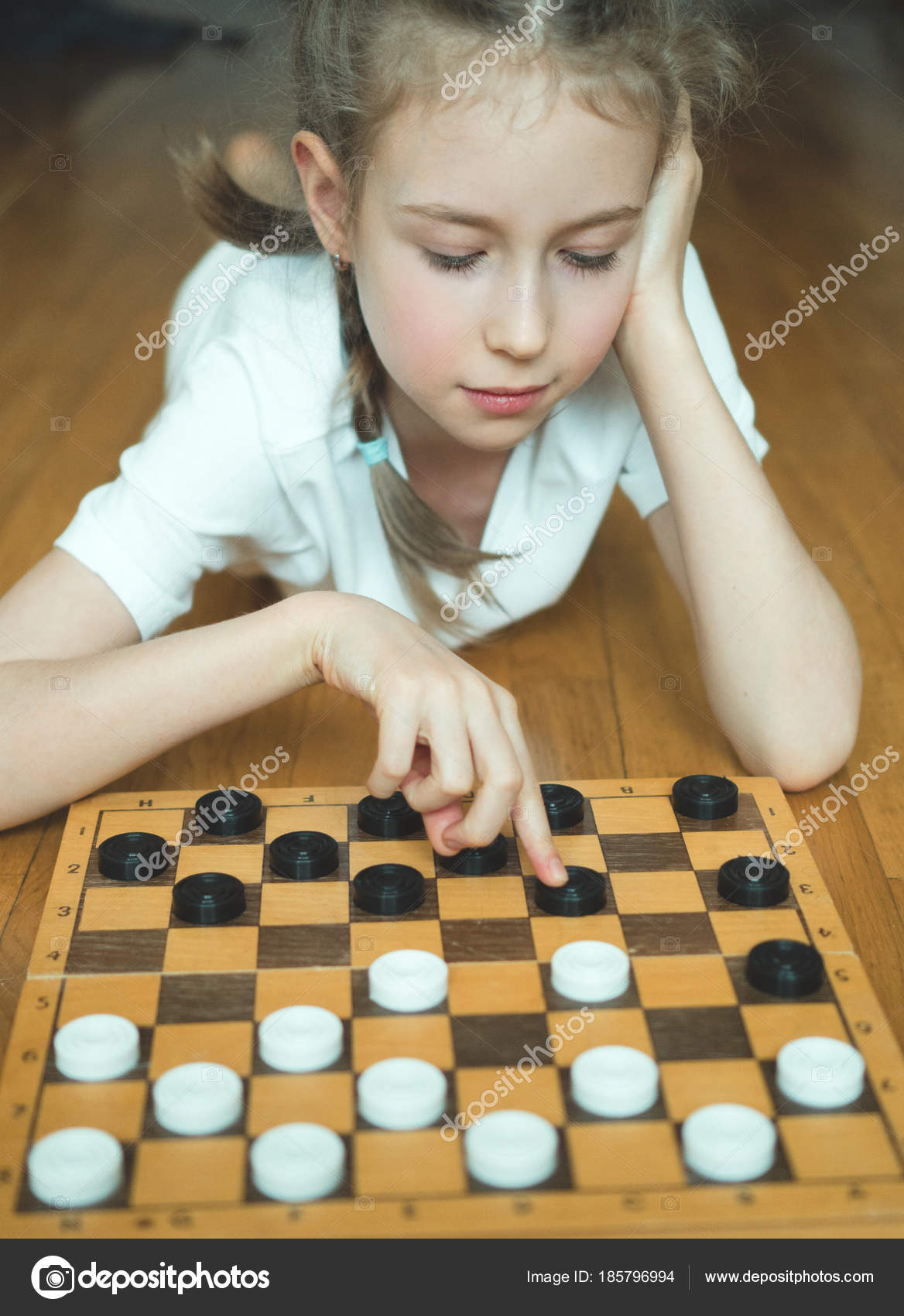 Little Cute Girl Playing Checkers Board Game Stock Photo