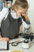 Little girl in science class using microscope.
