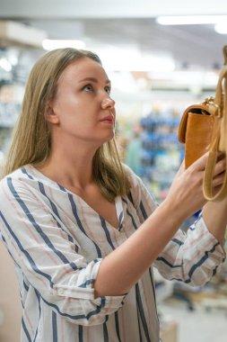 Young woman choosing bag in the shop.