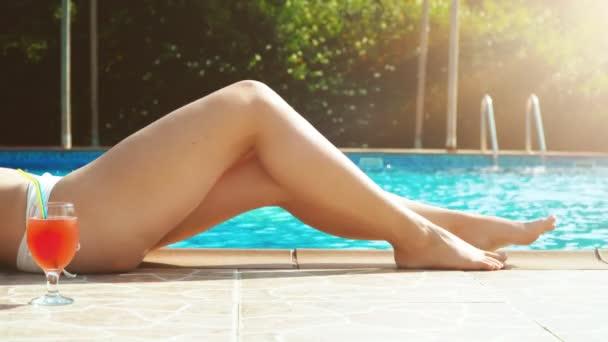 Nő koktéllal a medence mellett.