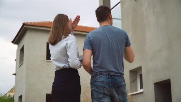 Pracovník hovořící s projektovým manažerem o projektu domu.