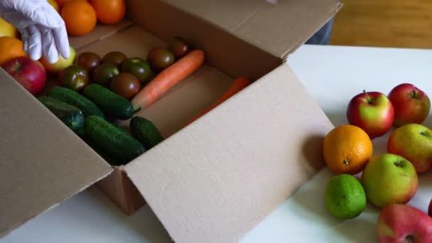 Dobrovolníci v ochranných lékařských rukavicích vybalují ovoce a zeleninu z dárcovské krabice.