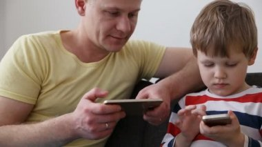 devices in the life of a modern family. dad with a small son playing games on smartphones, sitting on the sofa at home.