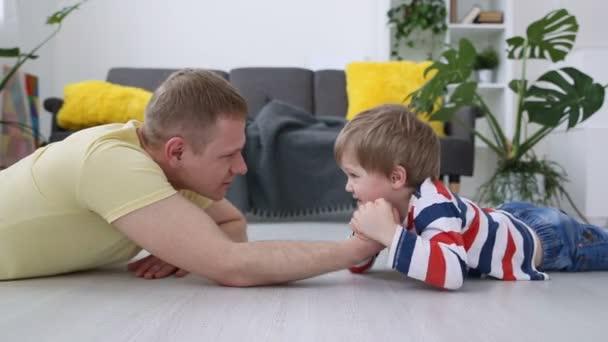 boldog modern család. Apa és fia, kis erő, az emeleten, a nappaliban mérik