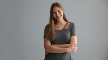 portrait of a blond girl of European appearance in casual clothes on a gray background
