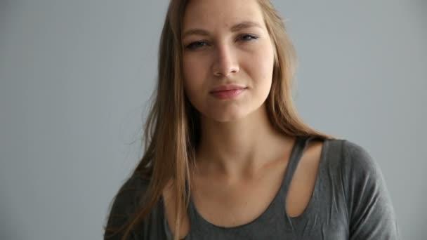portré egy szőke lány, európai megjelenés, alkalmi ruha, egy szürke háttér