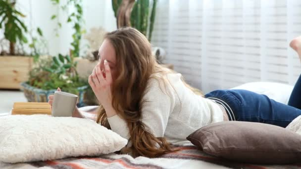 žena pije kávu a čte knihu v ložnici postel