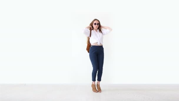fashion of modern youth. stylish girl posing against white wall in jeans, white shirt, with leather backpack and glasses.