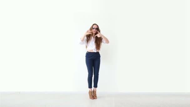 Módní moderní mládeže. elegantní dívka pózuje proti bílé zdi v džíny, bílé tričko s kožený batoh a brýle.