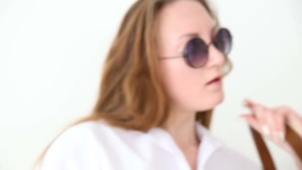 Módní moderní mládeže. elegantní dívka pózuje proti bílé zdi v džíny, bílé tričko s kožený batoh a brýle. Ruční natáčení
