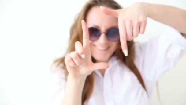 Módní moderní mládeže. elegantní dívka pózuje proti bílé zdi v džíny, bílé tričko s kožený batoh a brýle. Ruční natáčení.
