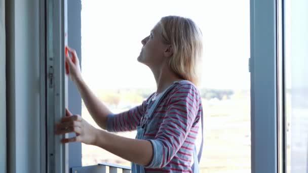 mladá žena čistí okno