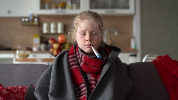 kaukasisches Mädchen zu Hause. Lustiges Porträt eines kranken Kindes in Schal und Karo mit Thermometer auf dem Sofa in der Wohnung