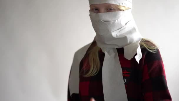 funny video - quarantined due to an epidemic of coronavirus. girl in a mask from toilet paper posing on a gray background.