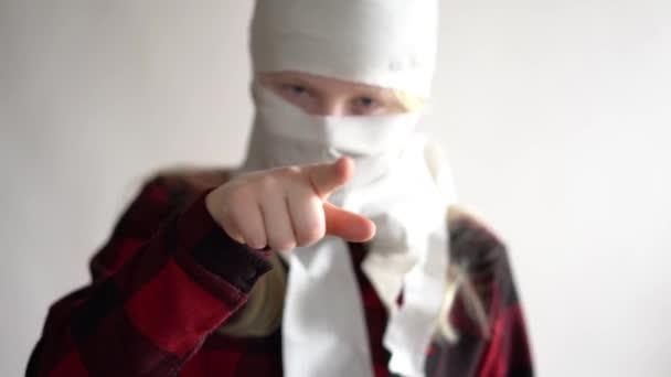 lustiges Video - Quarantäne wegen einer Coronavirus-Epidemie. Mädchen in einer Maske aus Toilettenpapier posiert auf grauem Hintergrund.