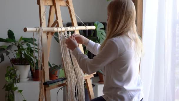 Zuhause bleiben. Arbeit während der Quarantäne - ein Mädchen im Wohnzimmer Wandmalerei Weben der Seile in Makrammatechnik