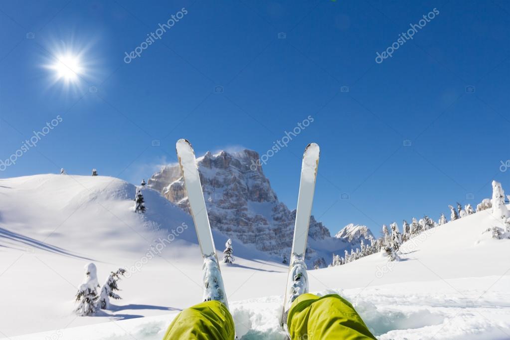 Detail of alpine skier legs, watching the valley panorama