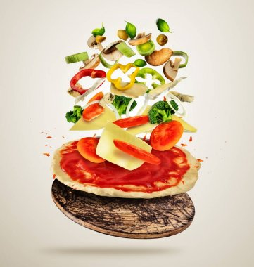 Flying ingredients with pizza dough, on creamy background