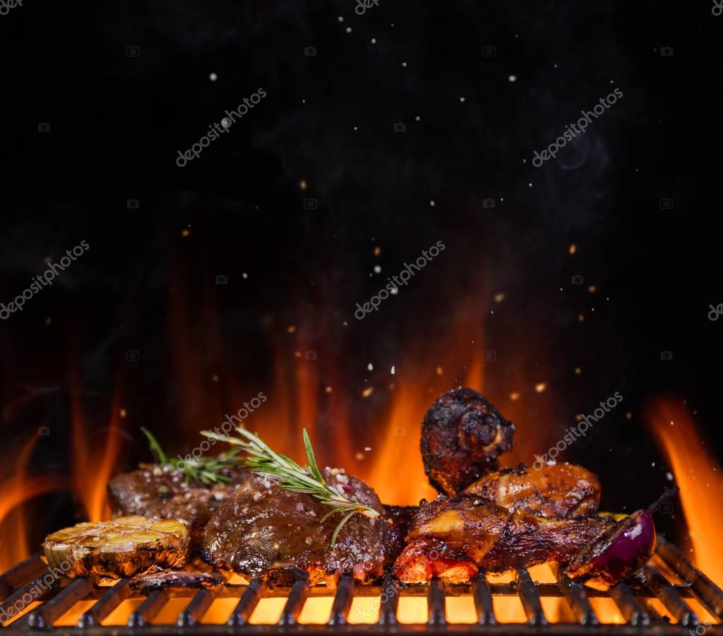 Beef steaks on the grill grate, flames on background
