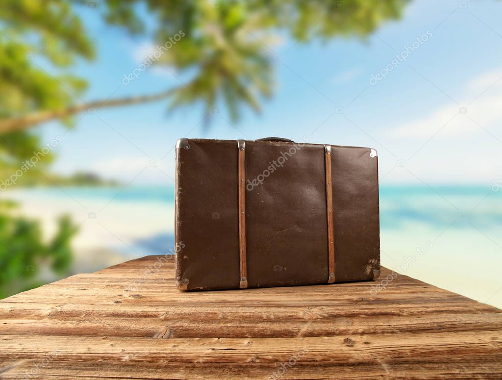 Retro luggage placed on wooden planks with tropical beach on bac