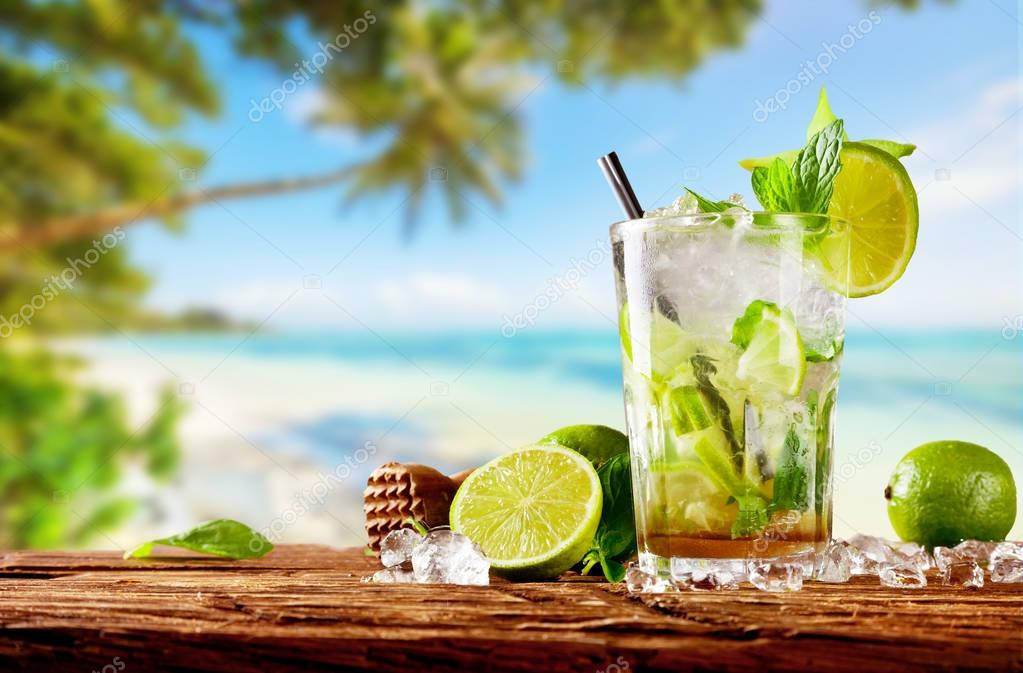 Fresh mojito drink placed on wooden planks, blur beach on backgr