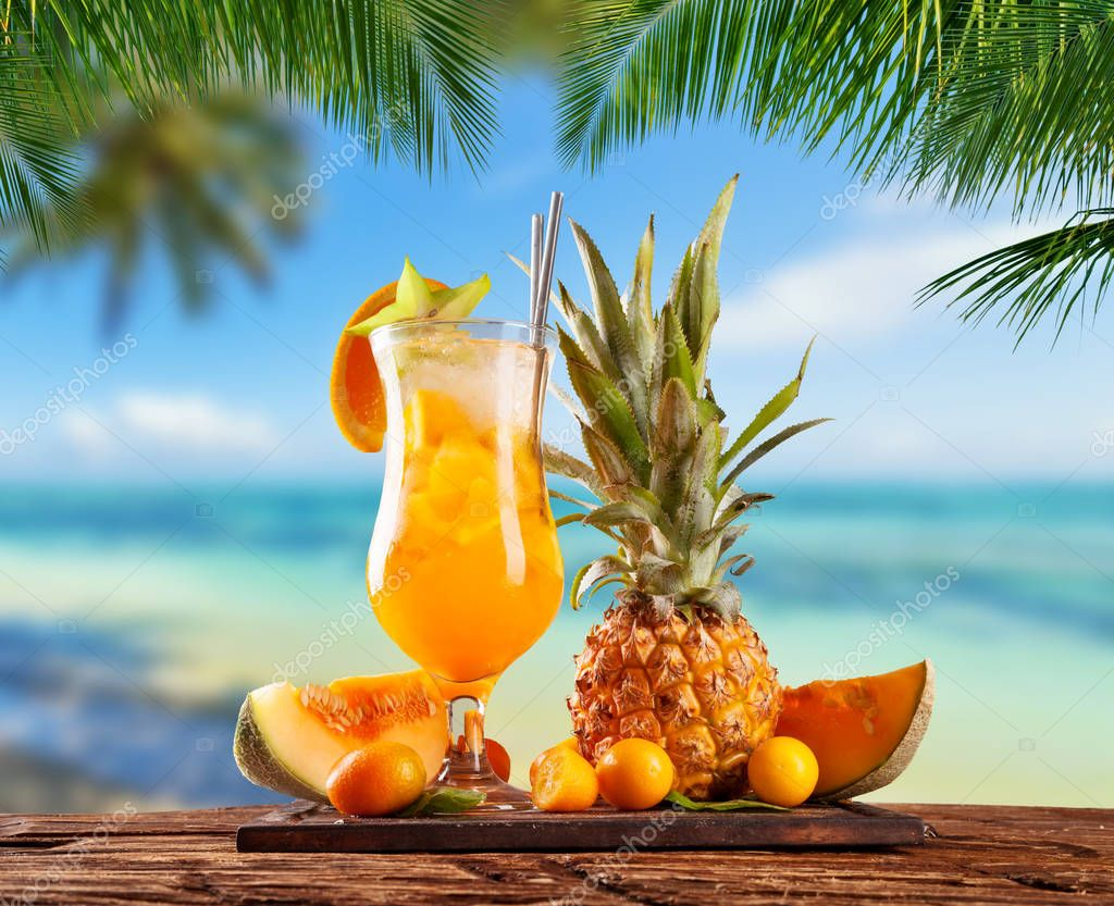 Fresh orange drink placed on wooden planks, blur beach on backgr