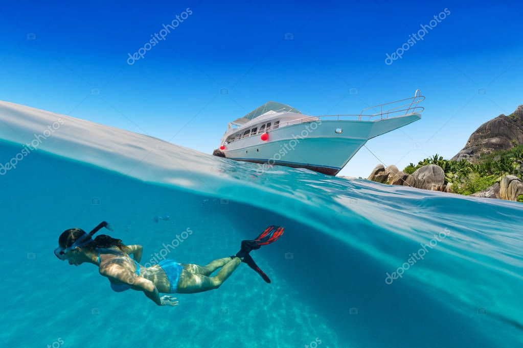 Small safari boat with snorkeling woman underwater.