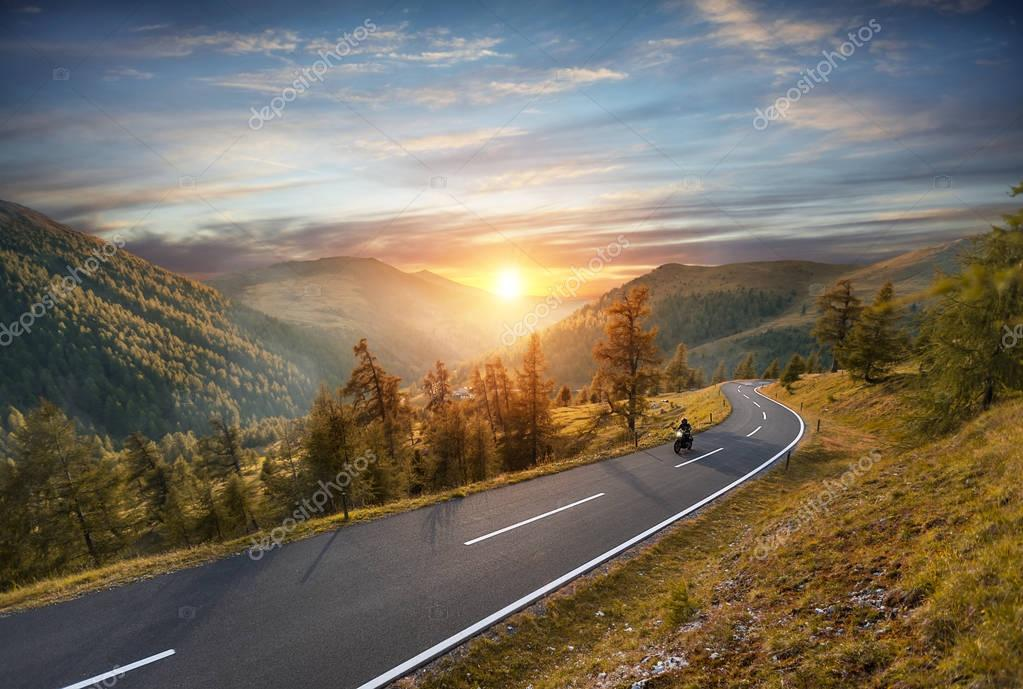 Motorcycle driver riding in Alpine highway. Outdoor photography,