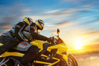 Motorbikers on sports motorbike riding in sunset
