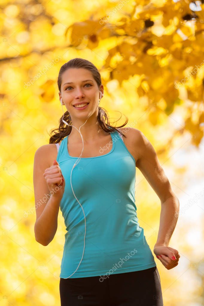 Young brunette woman running in autumn forest
