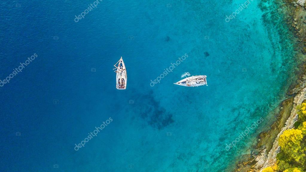 Aerial view of two sailing boats anchoring next to reef