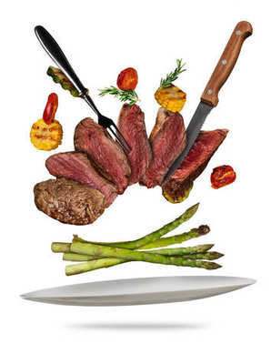 Flying beef steaks with grilled vegetable served on plate.