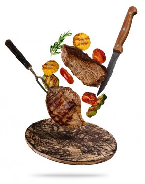 Flying beef steaks with grilled vegetable served on wooden cutti