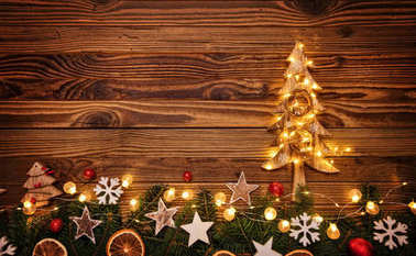 Christmas background with wooden decorations, tree and spot ligh
