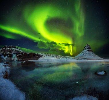 Kirkjufell mountain with beautiful aurora borealis and frozen wa