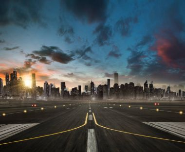 Empty airplane runway heading for the modern city with skyscrape