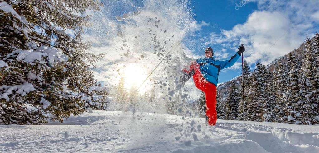 Young man walking on snowshoes in powder snow.