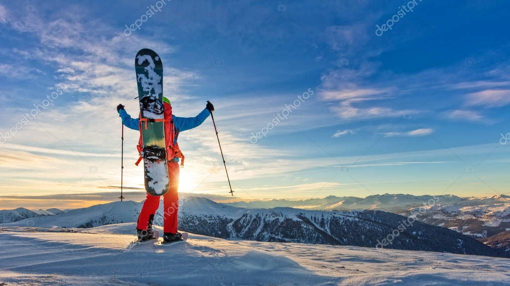 Snowboarder walking on snowshoes in powder snow.