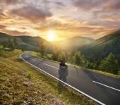 Motorbiker jízda v rakouských Alpách v krásný západ slunce dramatické
