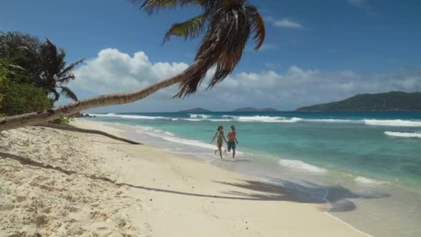 Paar junger Männer und Frauen beim Laufen am Strand der Seychellen auf der Insel Digue