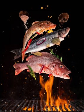 Flying raw whole fish from grill grid, isolated on black backgro