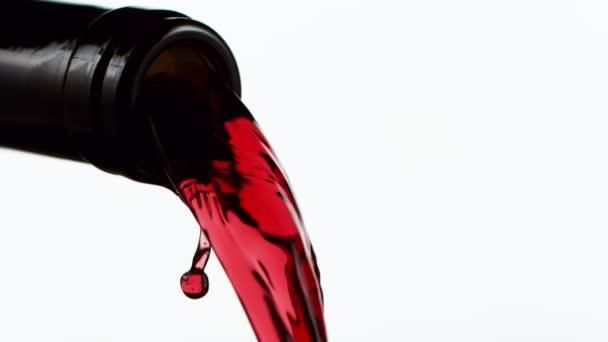 Super zpomalení nalití červeného vína v detailu, izolované na bílém pozadí. Natočeno na vysokorychlostní kameře, 1000 fps