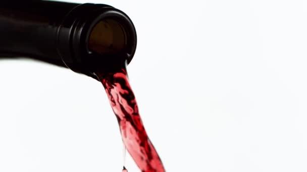 Szuper lassított mozgású öntés vörösbor részletesen, elszigetelt fehér háttérrel. Nagysebességű mozi kamera, 1000 fps