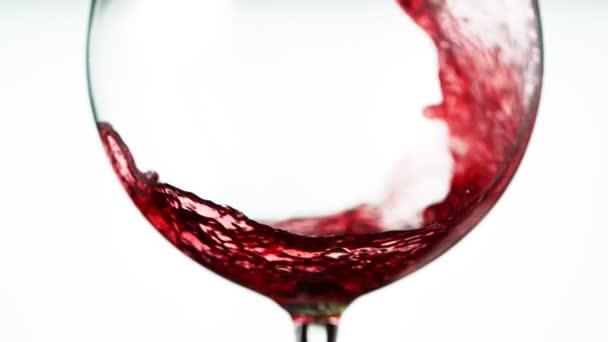 Super-Zeitlupe des Einschenken von Rotwein im Detail, isoliert auf weißem Hintergrund. Gefilmt mit High-Speed-Kinokamera, 1000 fps