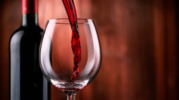 Super slow motion of pouring red wine with wooden background. Filmed on high speed cinema camera, 1000 fps