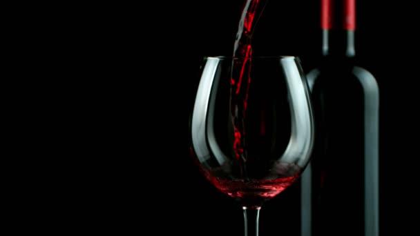 Super zpomalený pohyb nalití červeného vína na černé pozadí. Natočeno na vysokorychlostní kameře, 1000 fps