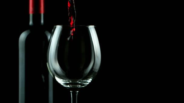 Superzeitlupe, in der Rotwein auf schwarzem Hintergrund ausgeschenkt wird. Gefilmt mit High-Speed-Kinokamera, 1000 fps