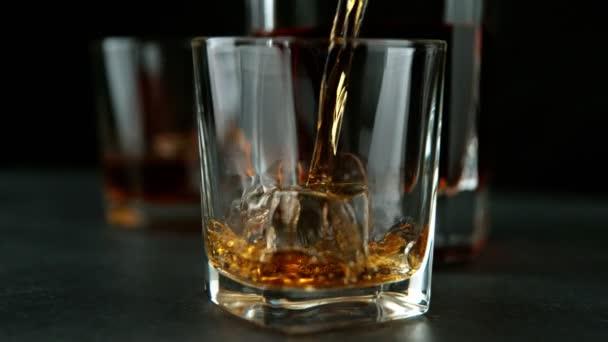 Super zpomalený pohyb nalévání whisky nebo rumu s posuvným pohybem. Natočeno na vysokorychlostní kameře, 1000 fps